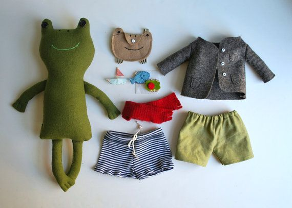 This sweet little froggy comes with all the accoutrement a frog needs to get by in the world: brown wool felt coat, sage green linen shorts, red wool scarf, stripey swim trunks, frog-head backpack, a little fish sandwich and a teeny paper boat. The frog is made from a recycled and washed secondhand suit coat in green wool. He has brown button eyes and webbed hands and feet. He has a hand-embellished classic brown coat made from wool felt--the coat has 3 hand-stitched pockets and 3 teeny…