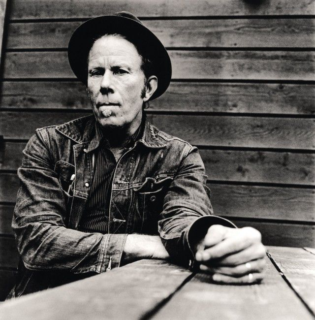 """Tom Waits,  American singer-songwriter, composer, and actor. Waits has a distinctive voice, described by critic Daniel Durchholz as sounding """"like it was soaked in a vat of bourbon, left hanging in the smokehouse for a few months, and then taken outside and run over with a car.""""[1] With this trademark growl, his incorporation of pre-rock music styles such as blues, jazz, and vaudeville, and experimental tendencies verging on industrial music,[2] Waits has built up a distinctive musical…"""