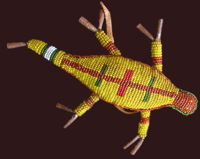 Sioux (replica) ca. 1870, applique' beadwork,white heart seed beads, tin cones, buffalo fur, etc.    This amulet was made for a boy and his umbilical cord was put inside (for a client in the USA)