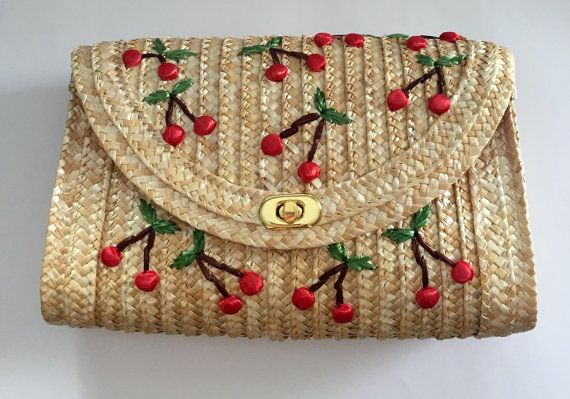 Super cute raffia straw clutch purse with cherry embroidery pattern. The lining is red and white plaid cotton and it closes with a snap closure.