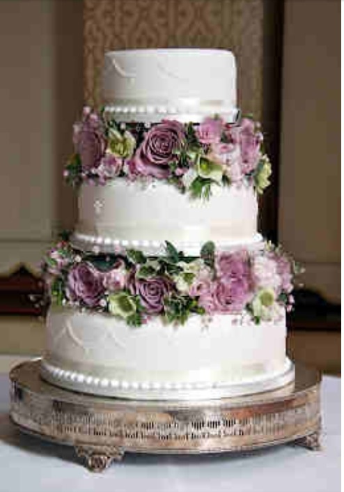 Vintage wedding cake with purple flowers.