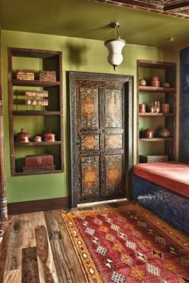 The door was hand-crafted and painted in Morocco. The niches on either side display various pieces of lacquerware from Burma, Afghanistan and India, as well as a Bhutanese jewelry box, Chinese pillow box and various other boxes from Asia.