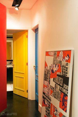 Na reforma total do apartamento dos anos 60, permaneceram apenas algumas paredes e o piso de taco. No chão do corredor, a madeira foi raspada e recebeu tingimento ebanizado. Foram instalados rodapés retos brancos de PVC. A grande bossa está nas portas de madeira que receberam tinta esmalte sintético nas cores amarelo e azul. A porta da rouparia central é em laca fosca vermelha. Outra sacada está na iluminação: trilhos pretos com spots direcionáveis. Para completar o espaço, um quadro…