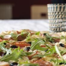 Pizza de rúcula, tomate seco y aceituna negra
