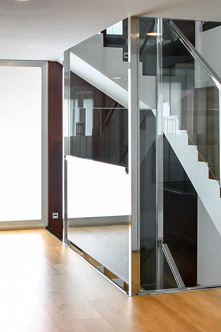 Chiralt Arquitectos I Escalera en vivienda moderna con barandilla de cristal.