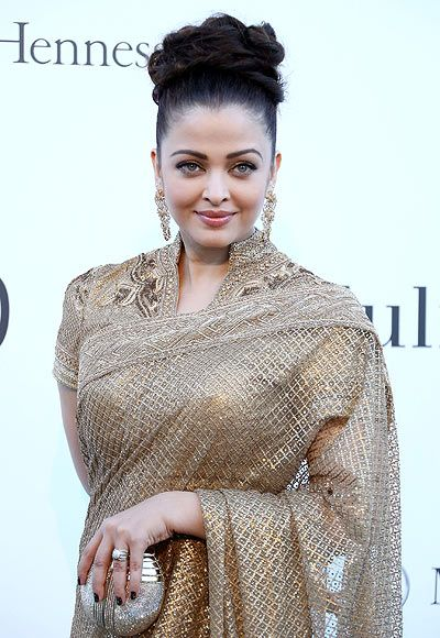 Get a closure on Aishwarya Rai Bachchan's look for amfAR Gala at Cannes 2013. She was sizzled in a gold Saree designed by Tarun Tahiliani with minimal makeup