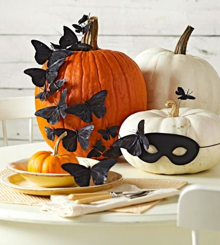 Fanciful pumpkins Fluttering butterflies alight on pumpkins in this attractive fall centerpiece. We spray-painted faux butterflies from a crafts store all black for a sophisticated look, then trimmed their wires to press into the pumpkins' skin. A harlequinlike mask adds whimsy.