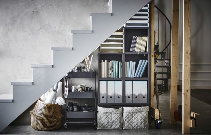 Home office supplies are stored under a staircase in a basket, a utility cart, and a bookshelf.