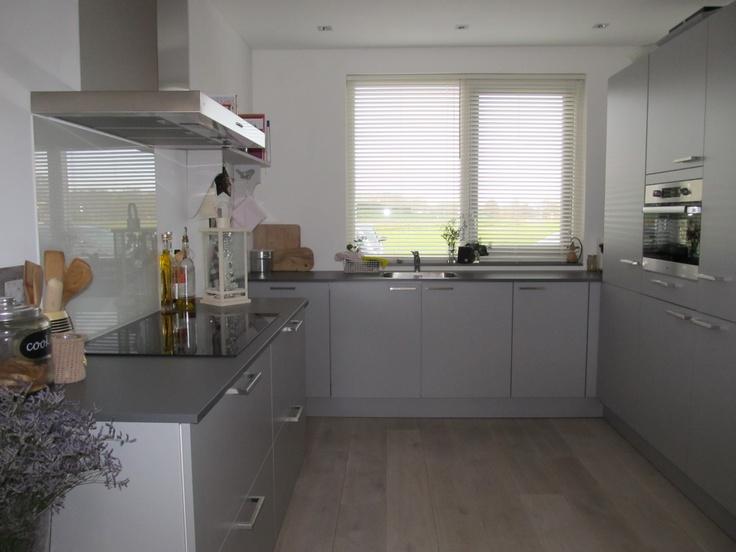Grijze keuken in ton sur ton met rvs apparatuur — in Dordrecht, Zuid-Holland.