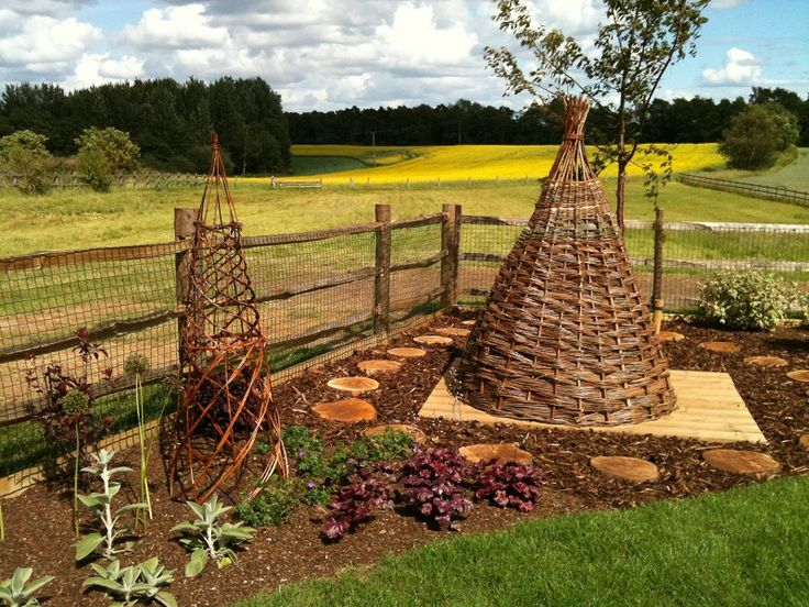 This bespoke, woven willow play house with log 'stepping stones' is a fun addition for the children as well as being charming, natural feature. Now all their friends want to come round to play! Willow obelisks for climbing plants were also commissioned for this border.