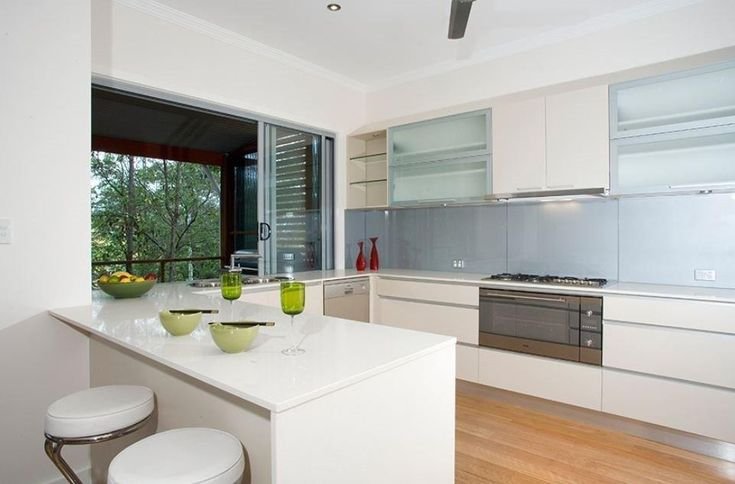Crisp white cupboards with light blue splashback - Kitchen Renovations Brisbane