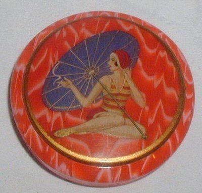 Celluloid powder compact which is the most amazing vibrant orange colour with a swirl of white and has a fabulous Art Deco design to the top of a flapper bathing belle.