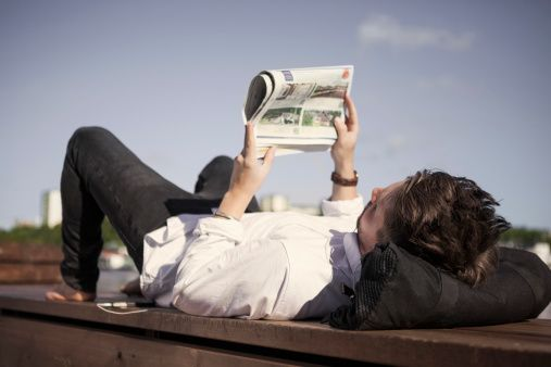 Businessman reading newspaper while lying on boardwalk