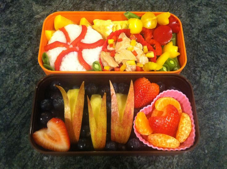 #108 Joanna USA A sweet bento full of sweet things. A candy mint of sticky rice and red bell pepper with chicken marmalade make up the main dish accompanied by yellow and red bell pepper candies on a bed of sugar snap peas. The desert side has three adorable apple bunnies swimming in a sea of blueberries with a few strawberry hearts and a side of sweet tangerine sections.
