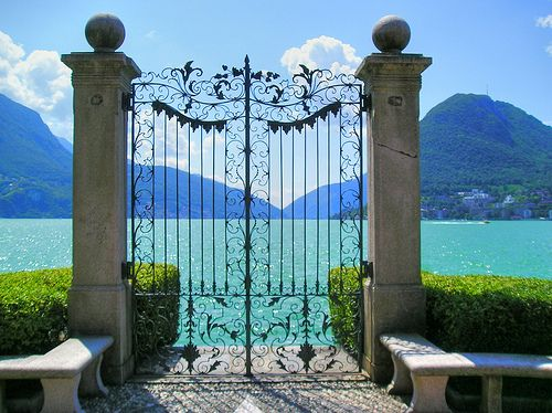 "A gate on the promenade in Lugano. It's a pretty random sight, since it doesn't really lead anywhere, but I guess its major function is to frame the beautiful lake and offer a kind of gates-of-heaven view onto Lago Lugano. As if that place is so beautiful that the gate kind of says ""only the worthy can go beyond here..."""