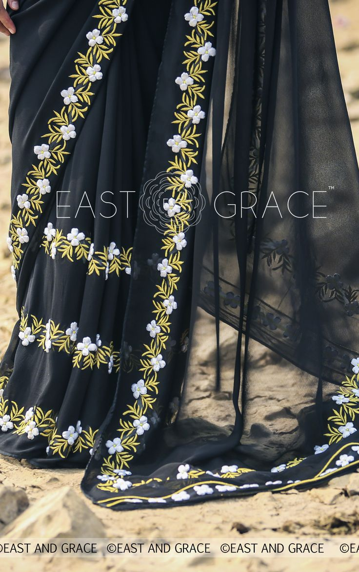 PRICE: INR 7,956.00; US$ 120.55 To buy click here: https://goo.gl/w855Sw Featuring the Black Buttercup saree in pitch black, 100% pure silk georgette with white ribbonwork buttercup flowers and golden thread embroidery leaves, that is perfect for evening affairs. The accompanying black blouse has a golden edging for an alluring finish. Brimming with vintage-inspired glamour, this saree is your staple of sorts. For help reach us at care@eastandgrace.com. With love www.eastandgrace.com