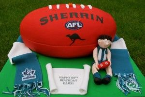 AFL Football Cake with a scarf, football and a player figure - cool footy birthday party cake - North Melbourne.