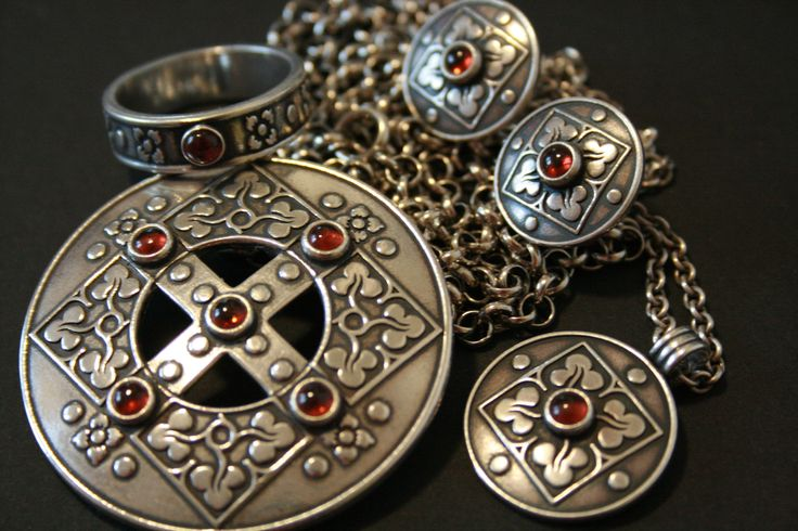 """""""Sankta Birgitta""""- serie including ring, post earrings and two necklaces where the bigger one is also a brooch. Silver and garnet. By Kalevala Koru. Finnish jewelry company."""