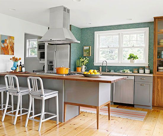 In a sea of grays and warm woods, a watery green backsplash creates a colorful focal point in this open kitchen. The glass tiles have a handmade look. Black grout, topped with a lighter grout, creates vintage-style variations between the tiles./