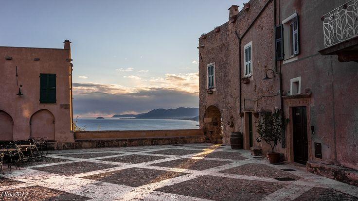 """Visitare Verezzi è come entrare in un teatro naturale, immerso nei caldi colori di Liguria e percorso dai sottili profumi della vegetazione mediterranea. Il borgo """"saraceno"""" si presenta  come armonioso insieme di quattro diverse borgate (Poggio, Piazza, Roccaro, Crosa), caratterizzate da costruzioni in pietra rosa incastonate in un panorama di roccia e di mare, interamente percorse e collegate dagli stretti """"caruggi"""" e """"creuze"""" un tempo destinati ai muli e ai carri. Le case addossate l'una…"""