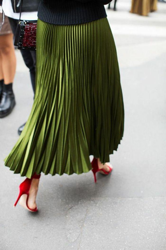tenue chic avec jupe plissée longue couleur olive portée avec des chaussures rouges à talons aiguilles