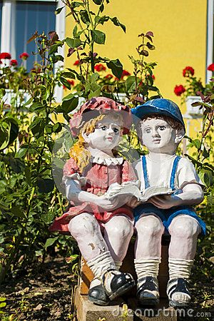 Picture of two stone garden figurine showing a boy & a girl reading a book