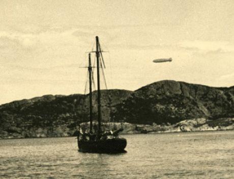 The Hindenburg seen in Brigus harbour, flying high above a schooner.
