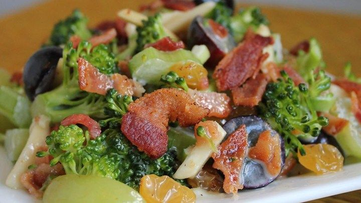 Broccoli florets, crumbled bacon, red and green grapes, raisins, and slivered almonds are all tossed in a creamy dressing for a delicious broccoli salad.