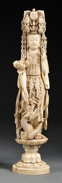 Kwan Yin,China, 19th century, in adorned clothing and headdress, left hand in the mudra of appeasement position, right hand holding a lotus blossom, a swirling dragon at feet, standing on a lotus base.
