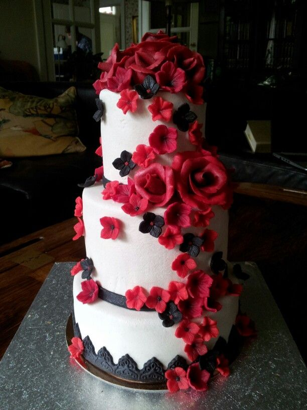 White wedding cake with a cascade of red and black flowers, all done in marcipan.
