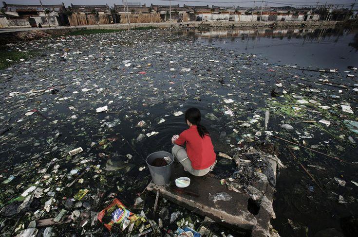 15. Une femme fait sa lessive dans un étang. Guiyu, une bourgade du Guangdong, est spécialisée dans le recyclage de produits électroniques et connue pour la pollution de ses cours d'eau.