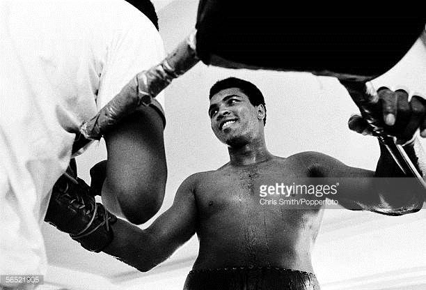 American heavyweight boxing champion Muhammad Ali being helped on with his gloves during a training session at Chris Dundee's 5th Street gym Miami...