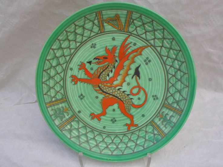 A scarce 1930s Crown Ducal wall plaque, designed by Charlotte Rhead, having a tube-lined decoration of a red enamelled 'Welsh' dragon, the border depicting a Celtic harp with overlapping stylized leaves and inset panels, on a green ground. This was not a commercially produced pattern and has no pattern number. Printed and tubed marks verso to include a Rhead facsimile signature and the decorator's mark for Fanny Morrey, 32cm diameter