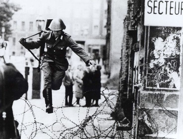 Soldado de Alemania Oriental saltando una valla de alambre de espino, 1961