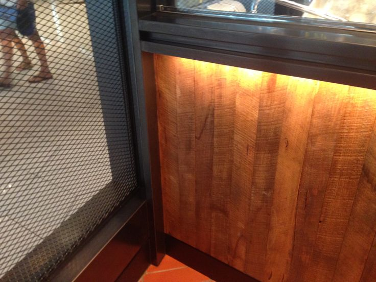 PHOTO 4: Timber back-lit skirting on the interior at San Antone. Looks like recycled wood but is made into a feature with the lighting and subtle texture added with the metal caging.
