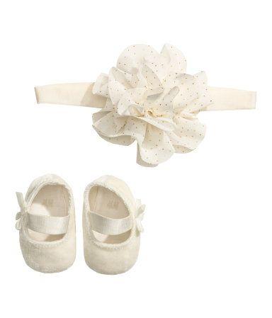 Naturhvit. Et sett med myke ballerinasko og hårbånd. Ballerinasko i velour med myk såle og tverrgående bånd oppå, og dekorativ sløyfe på siden. Elastisk