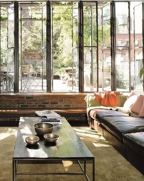 Salon esprit loft - grande baie vitrée cadre métal, soubassement en briques, canapé en cuir. #loft #living+room #windows