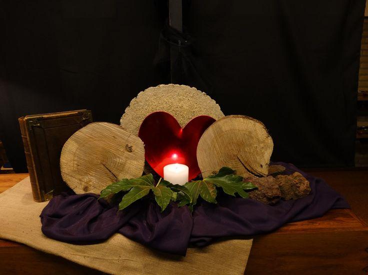 Witte donderdag 2017 De boomschijven staan voor :het moment dat alles verandert. De rode stukken hout zijn de deurposten die met bloed zijn bestreken. Het brood en de bittere kruiden die zij aten als laatste maaltijd. Het brood en wijn voor het laatste avondmaal met Jezus. Op de achtergrond het kruis, voor dat wat komen gaat. U Vader aanbidden wij wij zingen U ter eer.  Nav exodus 12 en marcus 14.