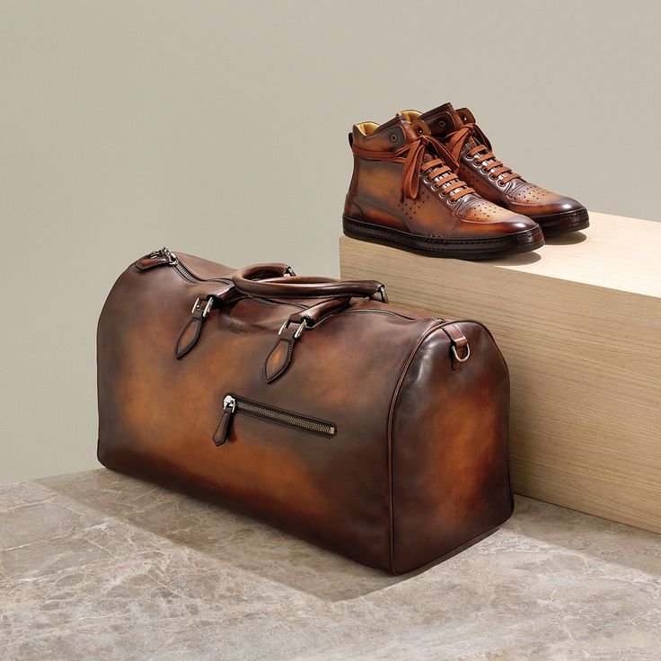 LEADER OF THE PACK. Berluti playtime high-top sneakers $2350. Jour-Off weekend bag $5235. Both in tobacco bis Venezia leather.