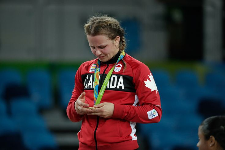 Erica Wiebe looks down at her gold medal while standing on the podium at Rio…