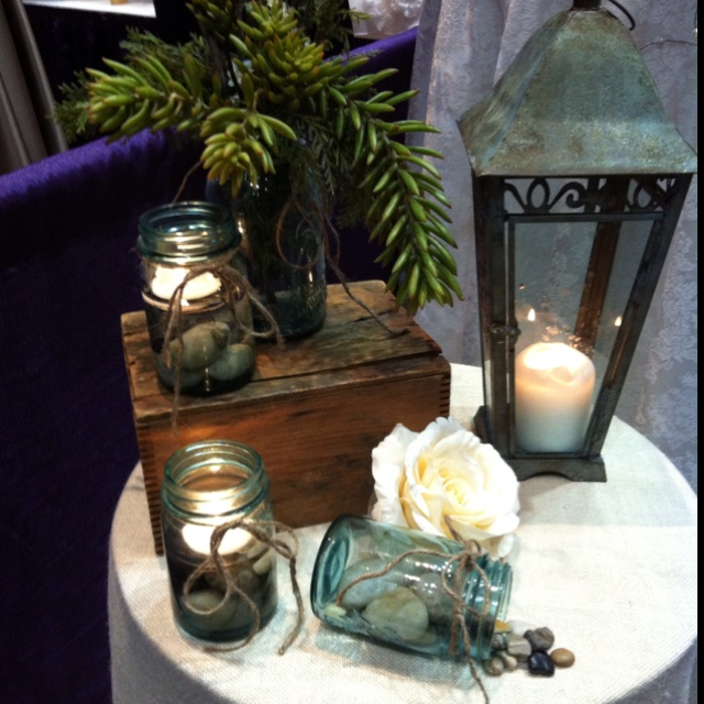 Love this setup for guest book table perhaps. Blue Mason jars with rocks and floating candles.