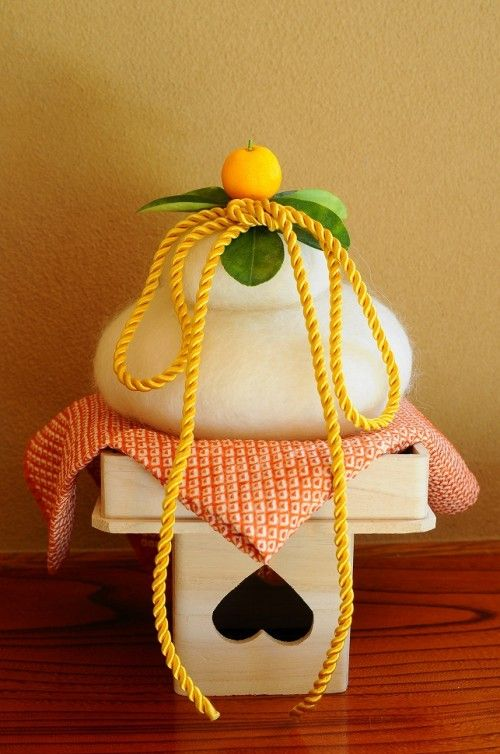 """Kagami mochi (鏡餅, """"mirror rice cake""""), is another significant, traditional Japanese New Year decoration. It usually consists of two round mochi (rice cakes), the smaller placed atop the larger, and a daidai (a Japanese bitter orange) or mikan (Japanese Tangerine)  with an attached leaf on top is placed on top of the Mochis.  