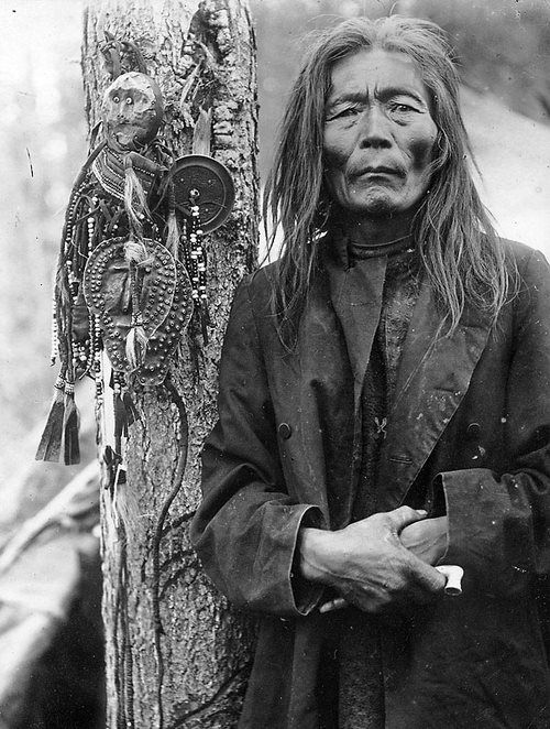 Evenk shaman with a collection of shamanic objects,   including images of helper spirits, early 1900s.  Russian Museum of Ethnography
