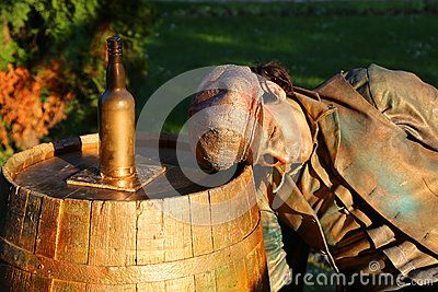 Living statue - sleeping near bottle at international festival of living statues in Bucharest, Romania.