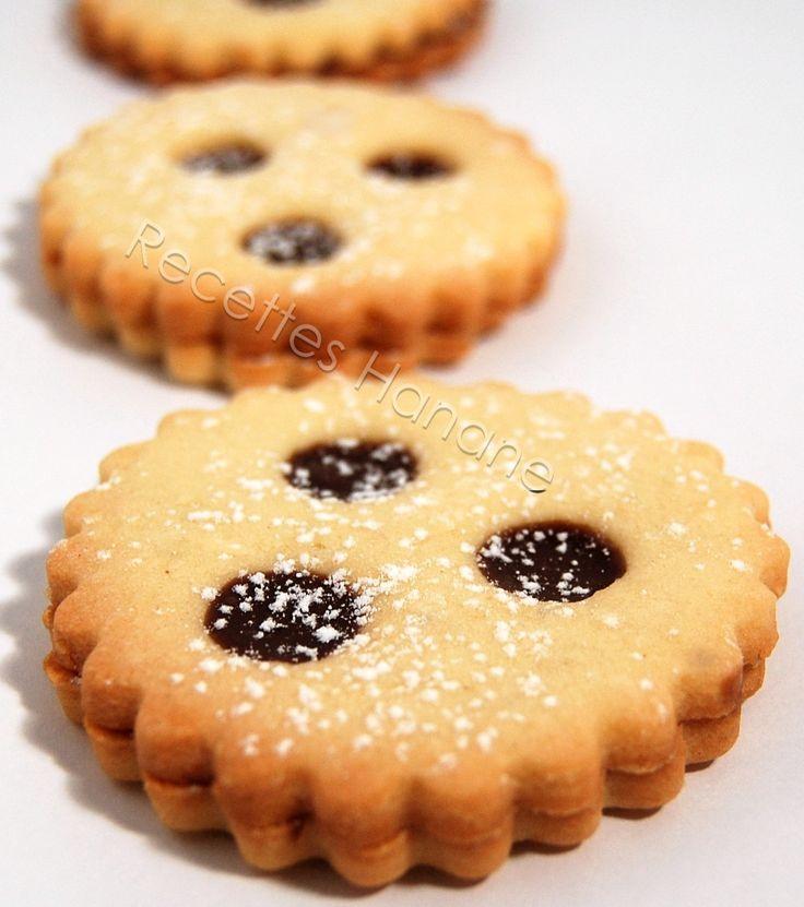 Des biscuits sablés, fondant en bouche, pour le goûter des enfants ou pour accompagner un café... 200g de farine 50g de maizena 30g de poudre d'amande 1 oeuf 150g de beurre mou 100g de sucre glace une pincée de sel pour la ganache: 200g de chocolat au...