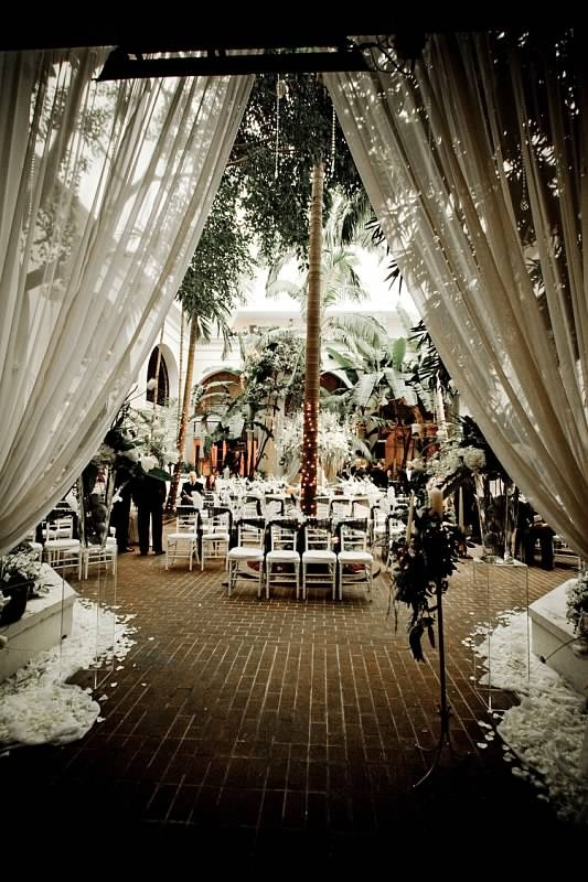 French Quarter Courtyard Weddings.  This is obscene with the flower waste but I like maybe shiny or white curtains.