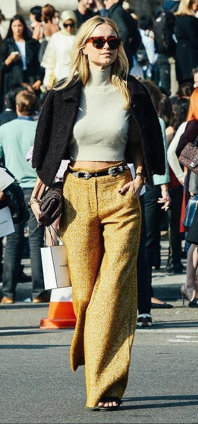Pernille Teisbaek in gold pants, cream cropped sweater, black overcoat