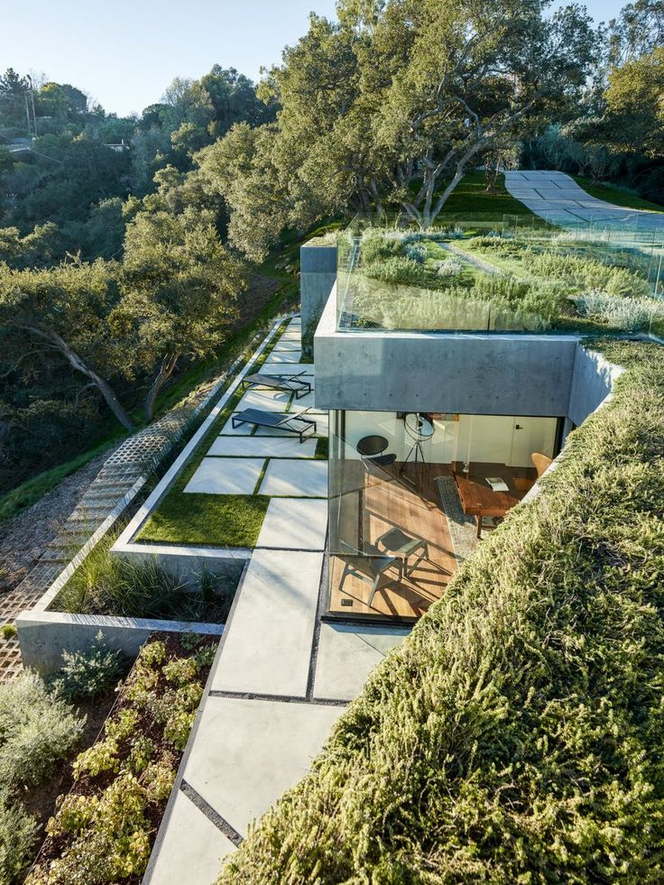 This 8,000-square-foot home is carefully integrated into the surrounding landscape, which includes more than 130 live oak trees. The bedrooms are buried into a hill and beneath a green roof of edible herbs.