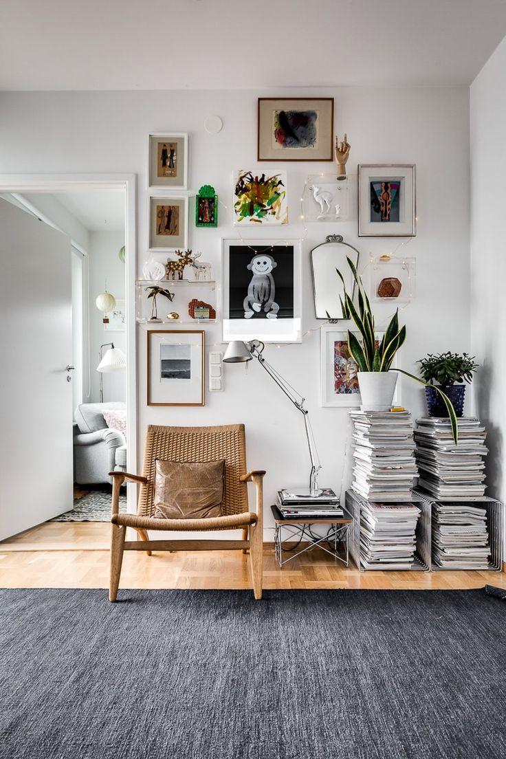 Un fauteuil scandinave tressé mis en valeur par ce mur de cadres parfaitement composé. Bonne idée pour un petit coin lecture dans un salon.