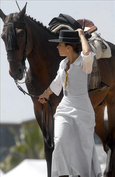 Beautiful dark horse and his lady, South of Spain! What a lovely outfit, cool white skirt and black hat.